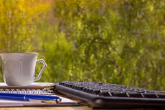 Coffee cup and computer keyboard on the wood texture Royalty Free Stock Images