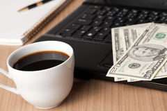 Coffee cup and computer with money Stock Image