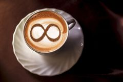Coffee cup concept infinity symbol. A cup of cappuccino coffee with a symbol of the symbol of infinity on milk foam stock images