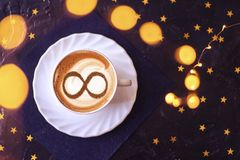 Coffee cup concept infinity symbol. A cup of cappuccino coffee with a symbol of the symbol of infinity on milk foam royalty free stock images