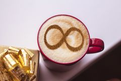 Coffee cup concept infinity symbol. A cup of cappuccino coffee with a symbol of the symbol of infinity on milk foam stock photography