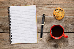 Coffee cup, cookie and notebook with pen Stock Photography