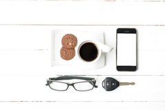Coffee cup with cookie,phone,eyeglasses and car key. On white wood table Royalty Free Stock Images