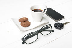 Coffee cup with cookie,phone,eyeglasses and car key. On white wood table Royalty Free Stock Photos