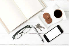 Coffee cup with cookie,phone,open notebook,key and eyeglasses Royalty Free Stock Images