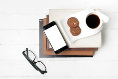 Coffee cup with cookie,phone,stack of book and eyeglasses Stock Photo