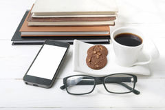 Coffee cup with cookie,phone,stack of book and eyeglasses Stock Photos