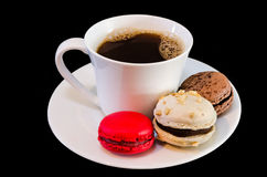 Coffee cup with macarons. Cookies on black background Royalty Free Stock Photo