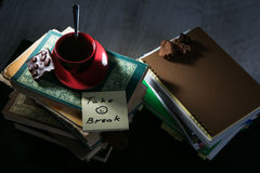 The coffee cup and cookies and chocolate and memo notes with message on stack of books royalty free stock photo
