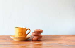 Coffee cup and cookies over wooden table.  Royalty Free Stock Image