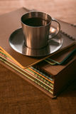 Coffee Cup with cookies is on the stack of notebooks stock images