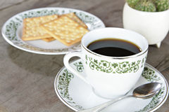 Coffee cup with crackers on wood table Stock Photo