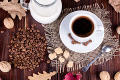 Coffee cup, cream, coffee grains and cane sugar Royalty Free Stock Images