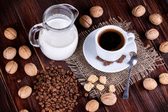 Coffee cup, cream, walnuts and cane sugar Royalty Free Stock Photos