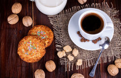 Coffee cup, cream, walnuts and oatmeal cookies Stock Photos
