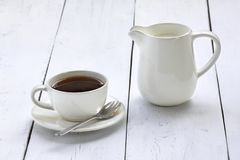 Coffee cup and creamer on a white table Royalty Free Stock Photo
