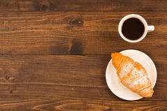 Coffee cup with croissant for breakfast on a dark wooden table, top view Stock Photography