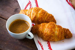 Coffee cup with a croissant on cloth Stock Images