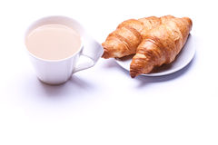 Coffee cup with a croissant. Isolated on wooden table . breakfast royalty free stock images