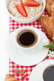 Coffee cup, croissant, oatmeal with strawberries and a sprig of Stock Photo