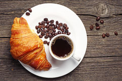 Coffee cup with a croissant. On vintage wooden table. Top view Stock Image