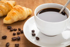 Coffee cup and croissants on wooden table Stock Photos