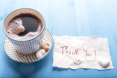 Coffee cup and cute thank you note. Paper note with a thank you message and a smiley face, a cup of hot aromatic coffee with pieces of heart shaped sugar, on a Stock Photo