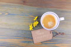Coffee cup and daisy flowers with wish cardboard label on wooden table. Have a nice day romantic message. Royalty Free Stock Photos