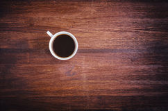 Coffee cup on dark brown wood table top view. Wood texture Royalty Free Stock Image