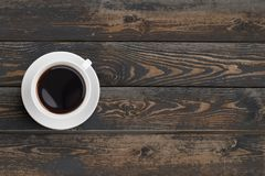 Black coffee cup on dark wooden table top view Royalty Free Stock Images