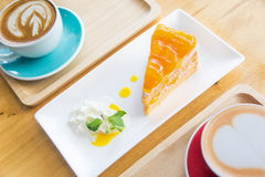 Coffee cup and Delicious orange cake in coffee shop. The coffee cup and Delicious orange cake in coffee shop royalty free stock image