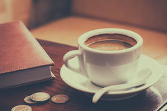 Coffee cup, diary and coins on table Stock Photography