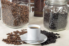 Coffee cup beside different types of roasted coffee beans Stock Photos