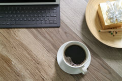 Coffee cup and Digital table dock smart keyboard,gold gift box a. Nd round wood tray,color pencil on wooden table,filter effect Royalty Free Stock Photos