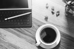 Coffee cup and Digital table dock smart keyboard,vase flower her. Bs,stylus pen on wooden table,filter effect,black white Royalty Free Stock Image
