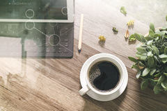 Coffee cup and Digital table dock smart keyboard,vase flower her. Bs,stylus pen on wooden table,filter effect,icons screen Stock Photos