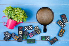Coffee cup, Domino and plastic flowers on the blue wooden backgr Royalty Free Stock Photo