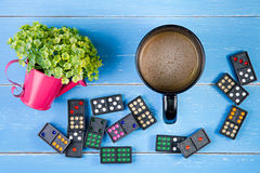 Coffee cup, Domino and plastic flowers on the blue wooden backgr Royalty Free Stock Photos