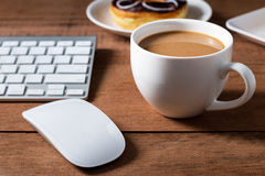 Coffee cup with donut and computer. Business concept Royalty Free Stock Photography