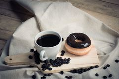 Coffee cup and donut with powder sugar icing on wooden board and Royalty Free Stock Photos