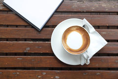 Coffee of cup and empty notepad. Put on wood table Royalty Free Stock Image