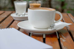 Coffee of cup and empty notepad. Put on wood table Stock Photography