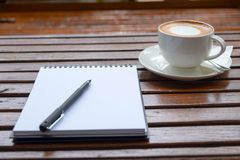 Coffee of cup and empty notepad on wood table. Coffee of cup and empty notepad wood table background Stock Photos