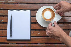 Coffee of cup and empty notepad on wood table. Coffee of cup and empty notepad wood table background Royalty Free Stock Photography