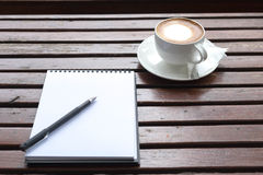 Coffee of cup and empty notepad. On wooden table Royalty Free Stock Photos