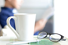 Coffee cup, eye glasses & pen over a book with blur background of a man Stock Image