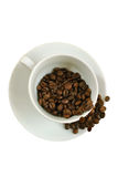 Coffee cup with falling coffee beans on white Royalty Free Stock Photos