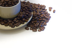 Coffee Cup filled with beans, overflowing. Coffee cup filled with coffee beans, overflowing on to saucer, and beyond, isolated on white Stock Photo