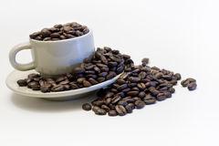 Coffee Cup filled with beans, overflowing. Coffee cup filled with coffee beans, overflowing on to saucer, and beyond, isolated on white Stock Image