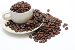 Coffee Cup filled with beans, overflowing. Coffee cup filled with coffee beans, overflowing on to saucer, and beyond, isolated on white Royalty Free Stock Photo